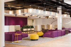 An open space with purple and yellow seating and tables