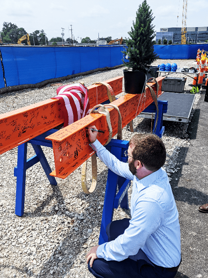 A man in a light blue shirt and dark blue pants sits on the ground in front of two orange beams, covered in signatures and propped up on blue sawhorses. He is signing one of the beams.